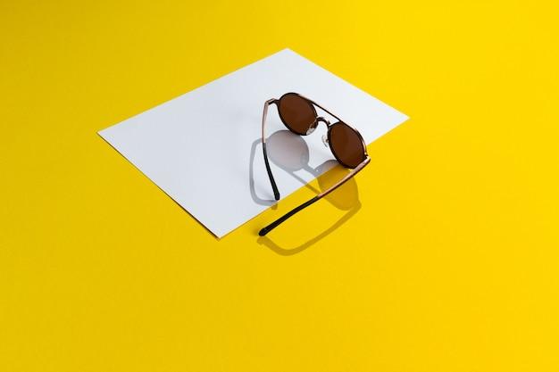 Occhiali da sole rotondi di classe unisex marroni alla moda su fondo di carta astratto bianco e giallo isolato con lo spazio della copia