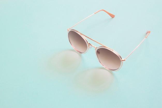 Occhiali da sole stile vintage alla moda su sfondo di colore pastello, moda minimal