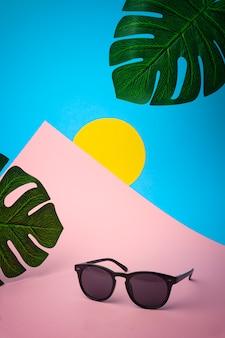 Occhiali da sole su uno sfondo colorato tropicale