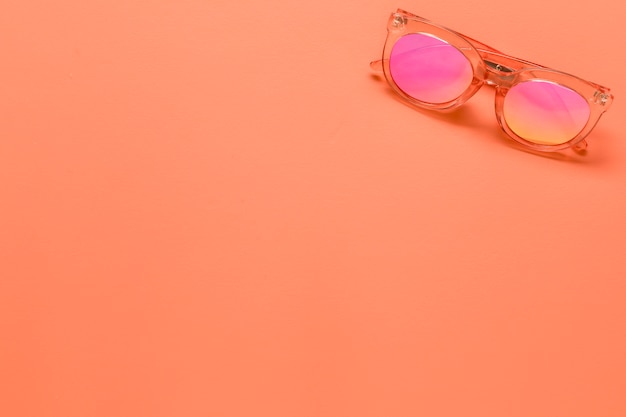 Occhiali da sole sulla superficie rosa