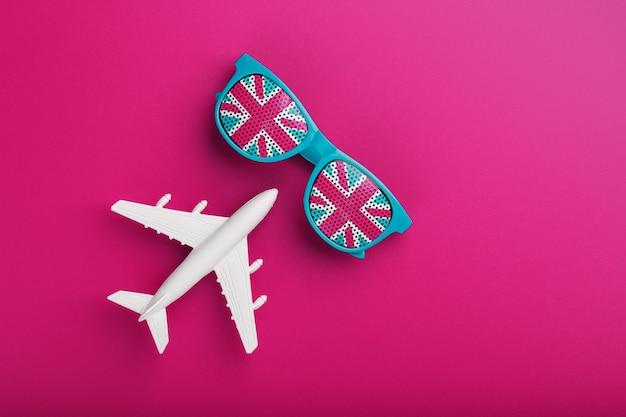 Occhiali da sole turchesi con bandiera del regno unito in lenti su pazza superficie rosa con aeroplano bianco