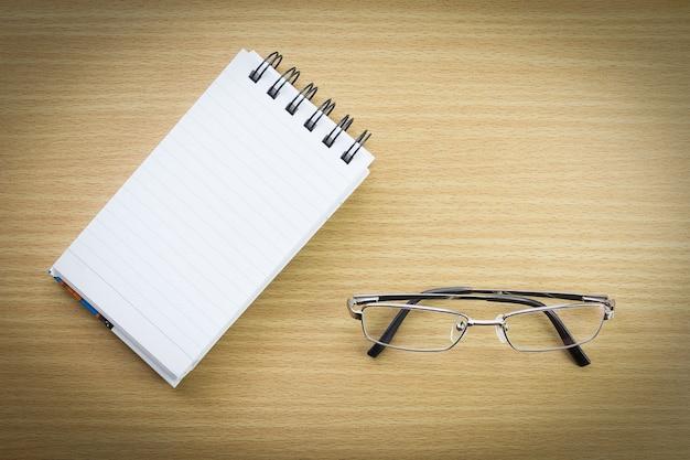 Occhiali da vista e blocco note con pagina vuota