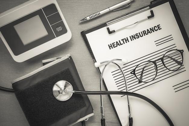 Occhiali da vista forma superiore assicurazione malattia e misuratore di impulsi con stetoscopio su sfondo in legno.