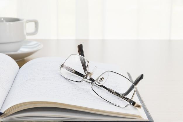 Occhiali da vista messi su un libro con sulla scrivania