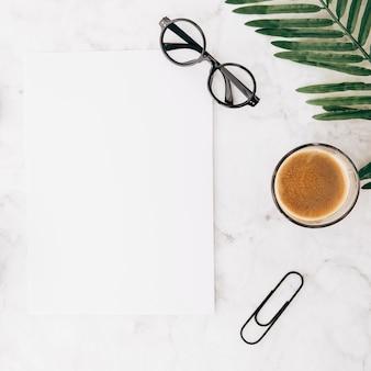 Occhiali da vista su carta bianca vuota con bicchiere di caffè; graffetta e foglie su fondo strutturato