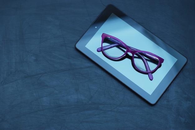 Occhiali da vista su tablet nel buio. educazione, technoogy, internet.