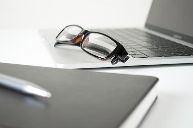 Occhiali da vista su un computer su un tavolo moderno in bianco con penna e taccuino.