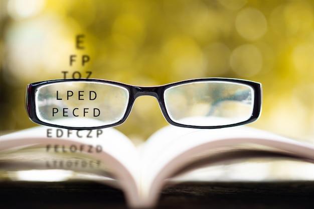 Occhiali da vista sul libro con diagramma di prova per la vista
