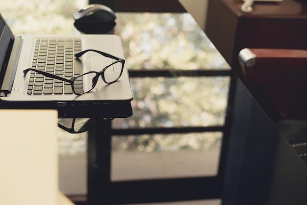 Occhiali da vista sulla scrivania con grafico e laptop sul posto di lavoro aziendale.