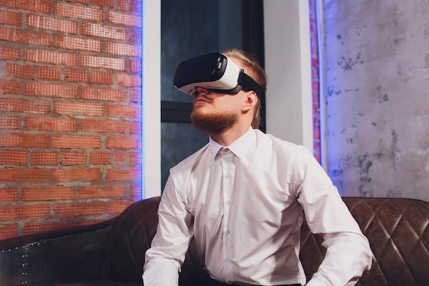 Occhiali di protezione da portare di realtà virtuale del giovane barbuto in studio coworking moderno.