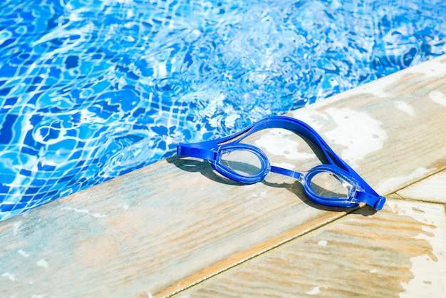 Occhiali di protezione dal lato di una piscina, concetto del fondo