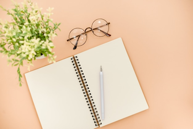 Occhiali e blocco note su uno sfondo astratto beige