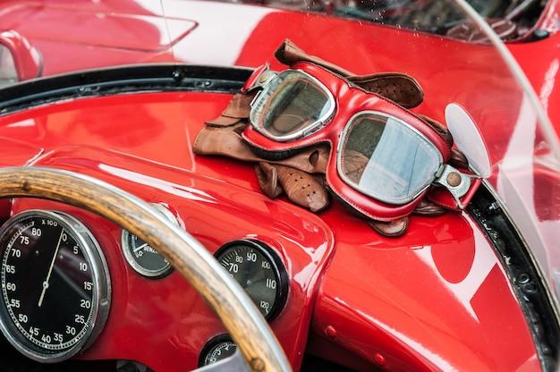 Occhiali e guanti all'interno di un'auto rossa d'epoca