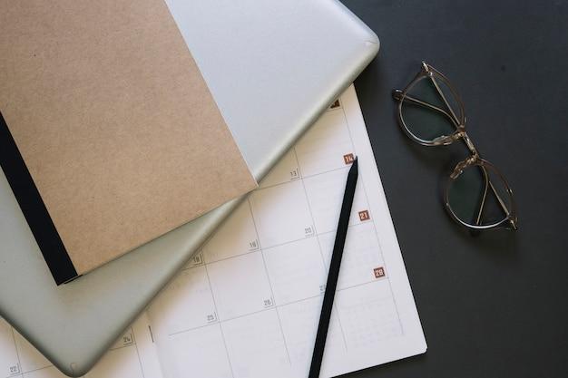 Occhiali e laptop vicino al calendario