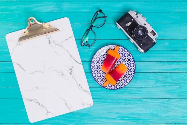 Occhiali e macchina fotografica e supporto e ghiaccioli sul piatto sulla superficie in legno