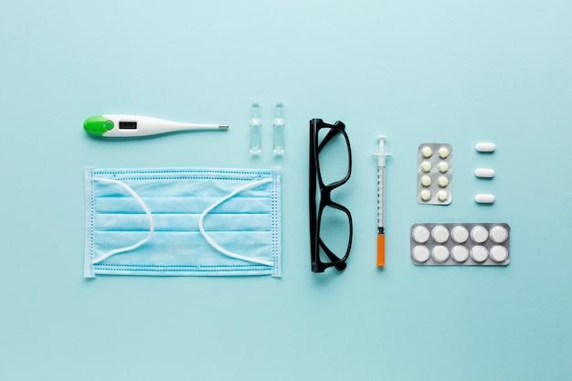 Occhiali e pillole sul computer portatile vicino allo stetoscopio sopra la superficie del blu