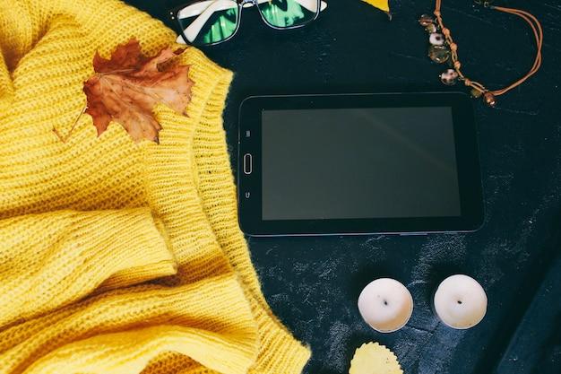 Occhiali e un maglione giallo brillante si trovano su uno sfondo scuro