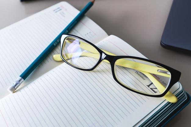 Occhiali e una matita sono sul quaderno. formazione scolastica. attività commerciale.