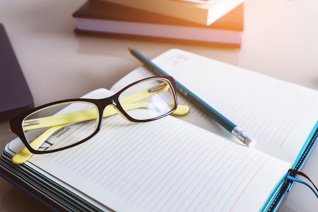 Occhiali e una matita su un quaderno, un diario. formazione aziendale