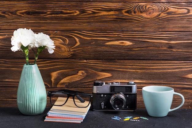 Occhiali; libri; graffetta per fogli; tazza e macchina fotografica d'epoca contro il contesto in legno strutturato