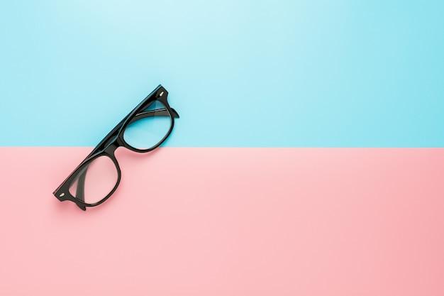 Occhiali neri su sfondo blu e rosa.