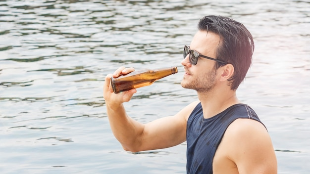 Occhiali neri uomo con una bevanda di bottiglia di birra in piscina