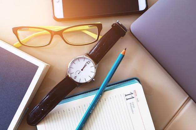 Occhiali, orologio e matita su un quaderno, diario. un telefono cellulare, un laptop e un libro.