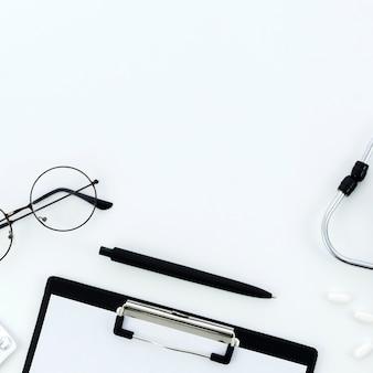 Occhiali; penna; appunti; pillole e stetoscopio su sfondo bianco