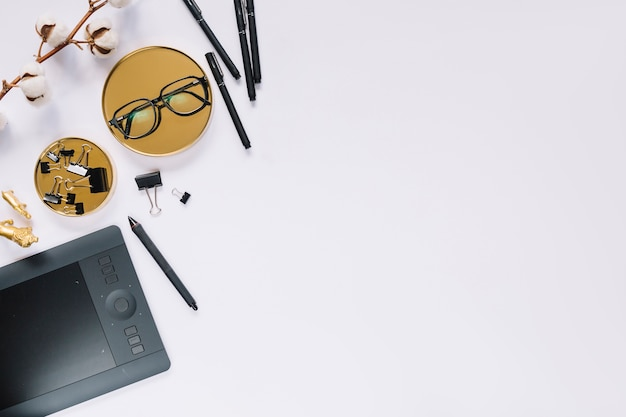 Occhiali; penna; bulldog clip; tavoletta grafica digitale e ramoscello di cotone sullo sfondo