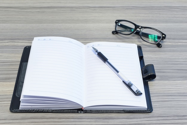 Occhiali, penna e diario aperto sulla scrivania