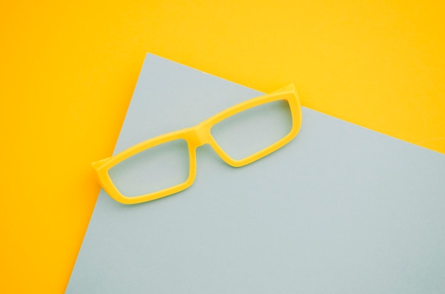 Occhiali per bambini gialli su sfondo grigio e giallo
