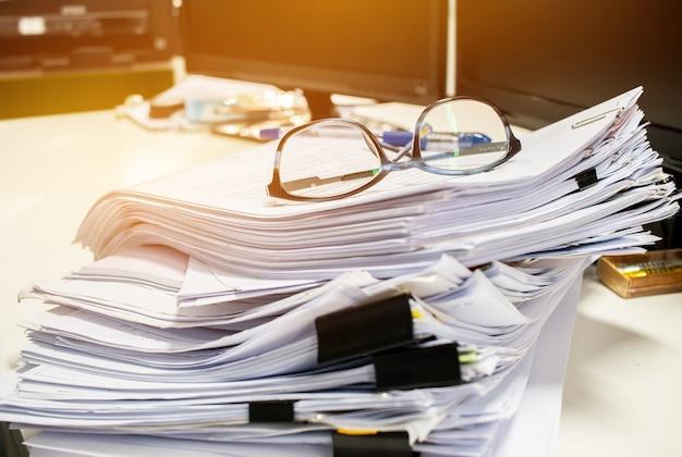 Occhiali posizionati su documenti non finiti pile di file di carta sulla scrivania del computer per la segnalazione