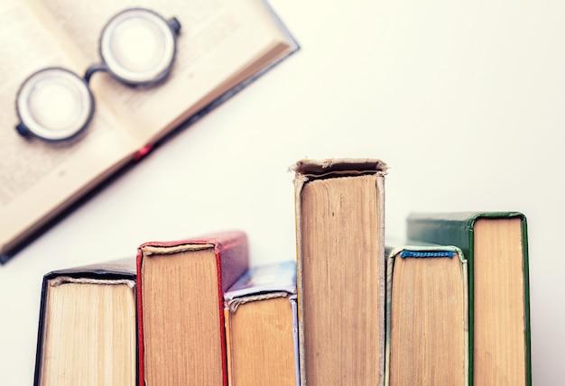Occhiali rotondi neri giacevano sopra una pila di vecchi libri malconci.