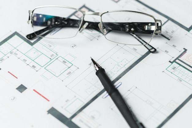 Occhiali sdraiati su un piano schematico di interior design