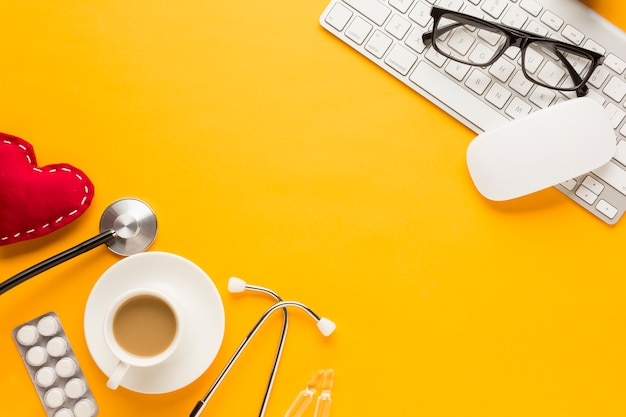 Occhiali su mouse e tastiera wireless con stetoscopio; cuore cucito; compressa imballata in blister e tazza di caffè contro la superficie gialla