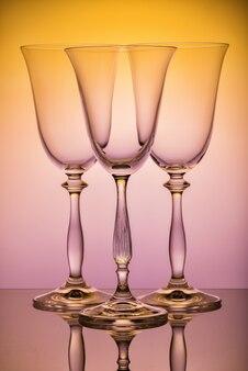 Occhiali su una gamba alta, sulla superficie dello specchio del tavolo, su uno sfondo giallo-rosa.