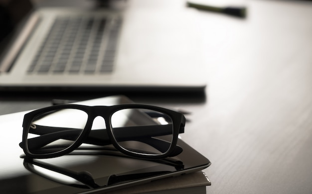 Occhiali sul tavolo ufficio con notebook computer