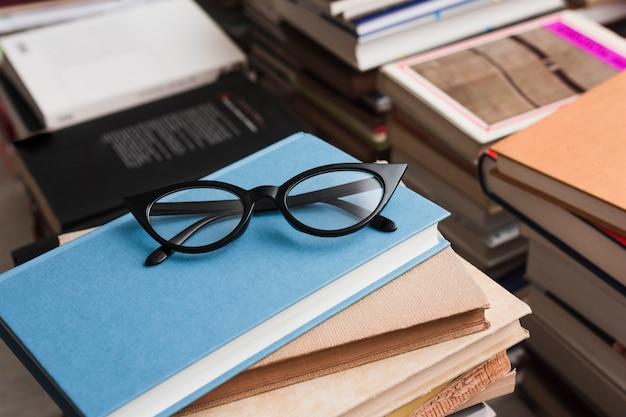 Occhiali sulla pila di libri