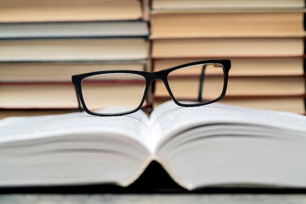 Occhiali sullo sfondo dei libri. simbolo di conoscenza, scienza, studio, saggezza.