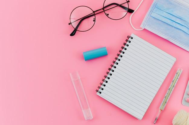 Occhiali; termometro; maschera chirurgica e quaderno a spirale su sfondo rosa