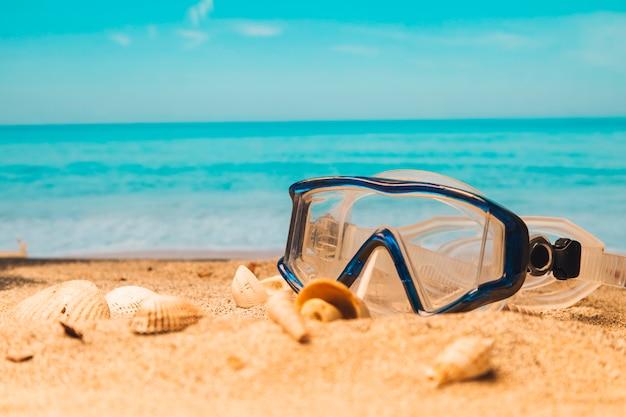 Occhialini da nuoto sulla spiaggia di sabbia