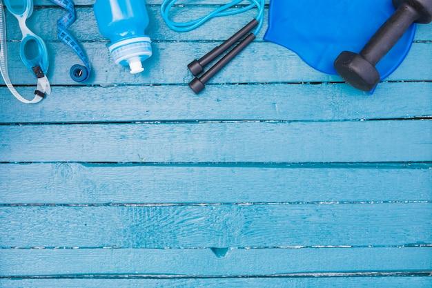 Occhialini; nastro di misurazione; bottiglia d'acqua; corda per saltare e manubri su fondo in legno
