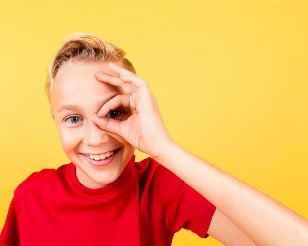 Occhio della copertura del ragazzo di smiley di vista frontale con il segno giusto