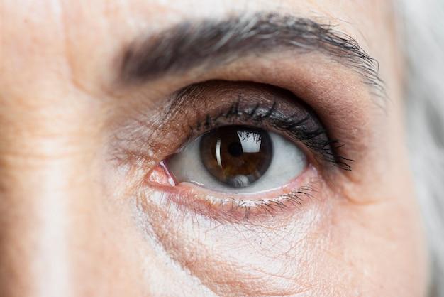 Occhio della donna del primo piano che esamina macchina fotografica