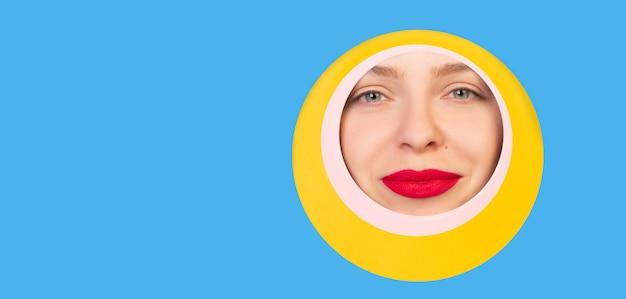 Occhio femminile che guarda, sbirciando attraverso il cerchio nel fondo blu