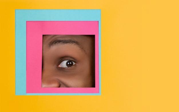 Occhio maschio che guarda, dante una occhiata in tutto il quadrato nel fondo arancio