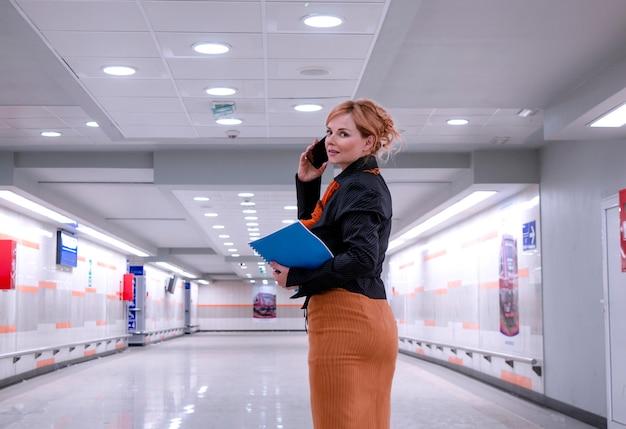 Occupato amministratore delegato della donna nella hall of business building utilizzando il telefono e controllando il file di documenti. donna d'affari in moderni hallaway andando a lavorare