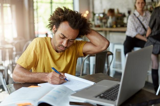 Occupato studente afroamericano seduto in caffetteria affrettandosi a scrivere note nel suo quaderno utilizzando il computer portatile per la ricerca di informazioni grattandosi la testa con la mano. istruzione, concetto di gioventù