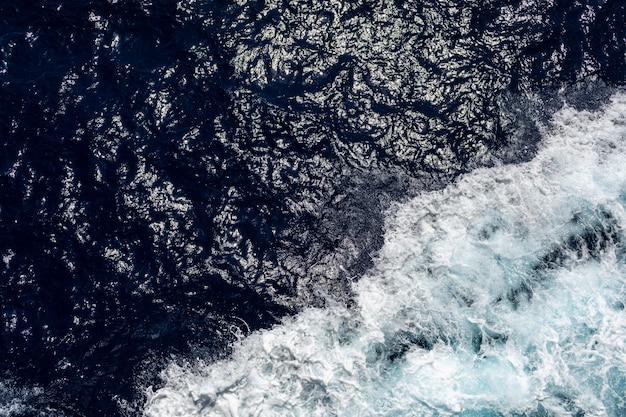 Oceano o mare con acqua blu in una giornata di sole. onde, schiuma e scia causate dalla nave da crociera nel mare, effetto immagine filtrata per il concetto di business del turismo, blog di crociere a vela, siti web di riviste
