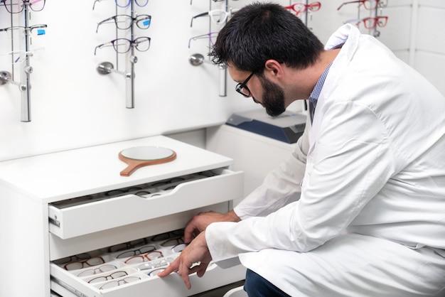 Oculista che sceglie gli occhiali da un cassetto nel negozio di ottica